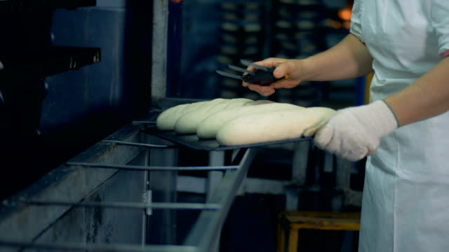 a worker prepares bread loaves for banking and makes surface cuts. - formare pane video stock e b–roll