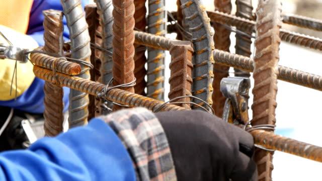 worker preparing bundle wire on steel bar in construction site - spranga video stock e b–roll