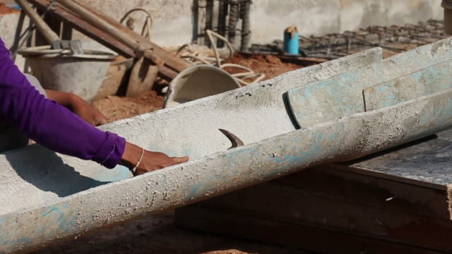Worker preparing pipe for cement pouring at construction site