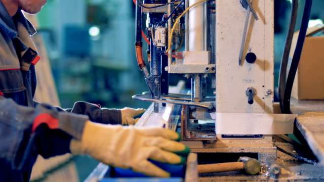 Worker processing plastic detail at industrial machine. video