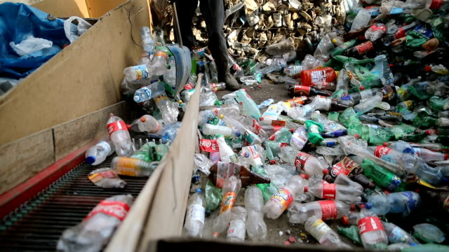 Worker pushes plastic bottles with a shovel for recycling.Working at a recycling factory