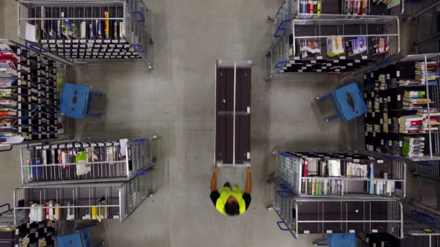 Worker pushing trolley on aisle in logistic center Overhead drone footage of manual worker pushing trolley on aisle in logistic center. Books are arranged on trollies at warehouse. Aerial video of male and female colleagues working in industry. storage room stock videos & royalty-free footage