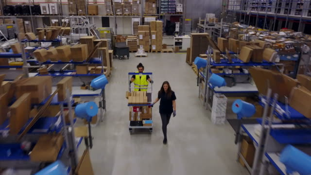Worker pushing trolley with coworker in warehouse Drone video of worker pushing trolley while walking with colleague on aisle in logistic center. Male and female are working amidst desks with cardboards and machineries They are in industry. storage room stock videos & royalty-free footage