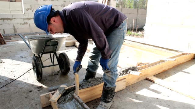 Worker puts concrete in the formwork with the help of a masonry trowel.