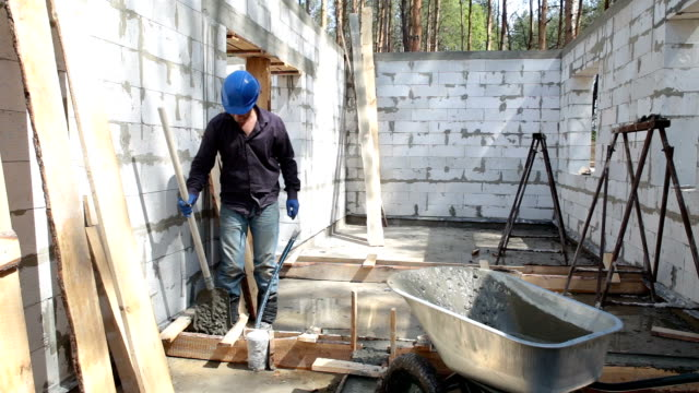 Worker puts concrete in the formwork with the help of a shovel.