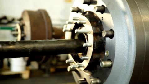 vidéos et rushes de le travailleur met le long arbre en métal à l'intérieur de la partie cylindrique de camion - lourd