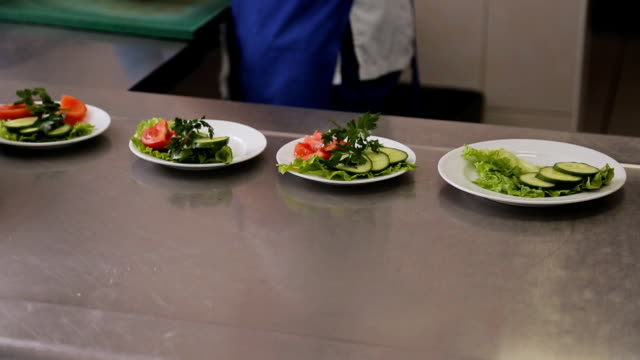 A worker puts slices of vegetables on plate closeup video