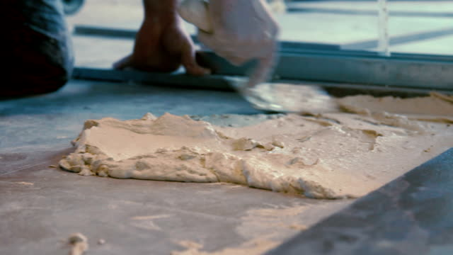 Worker putting cement gum and tiles adhesive on the floor before laying ceramic tile video