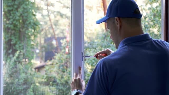 worker repairing and adjusting plastic pvc window - okno filmów i materiałów b-roll
