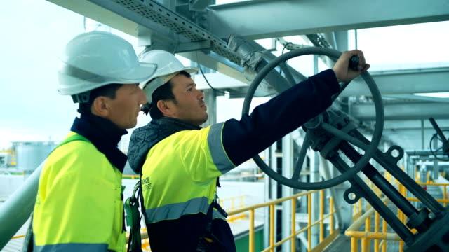 stockvideo's en b-roll-footage met werknemer roterende wielen op grote olieraffinaderij - raffinaderij