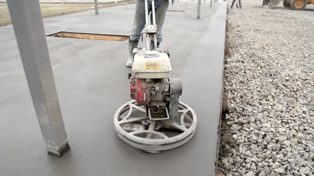 Worker smoothes concrete surface video