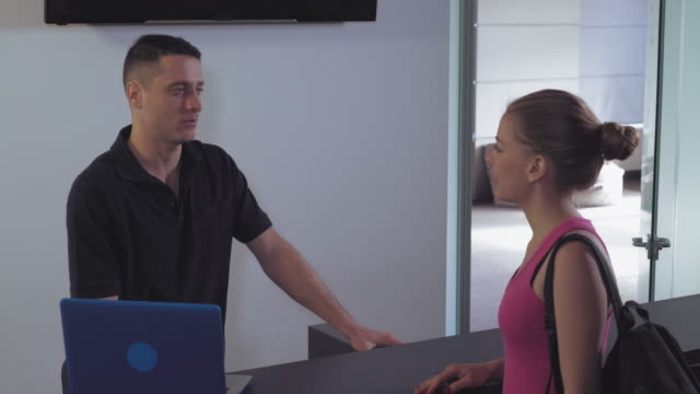 Worker speaking with client in gym video