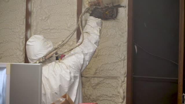 worker spraying closed cell spray foam insulation - gommapiuma video stock e b–roll
