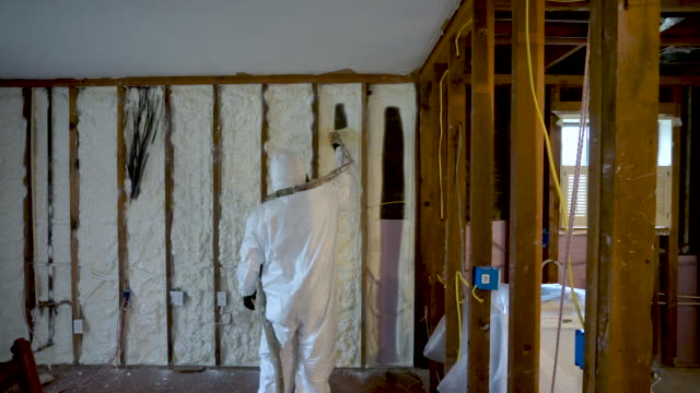 worker spraying closed cell spray foam insulation - poliuretano polimero video stock e b–roll