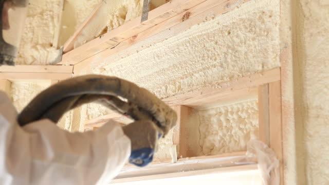 operaio spruzzare espandibile materiale espanso isolante tra wall borchie - gommapiuma video stock e b–roll