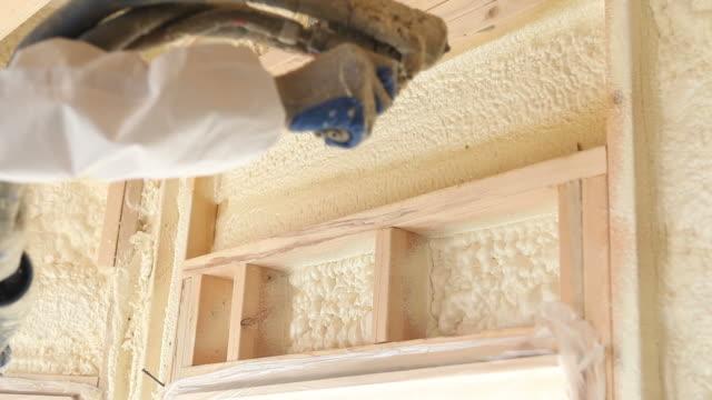 vídeos de stock e filmes b-roll de trabalhador pulverizar expansível espuma de isolamento entre pitons de parede - pulverizar