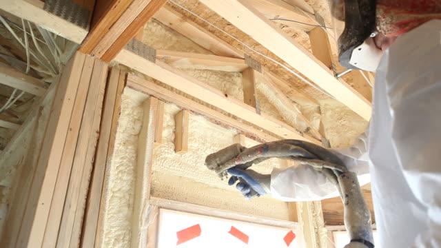 vídeos de stock e filmes b-roll de trabalhador pulverizar expansível espuma de isolamento na janela de cabeçalhos - pulverizar
