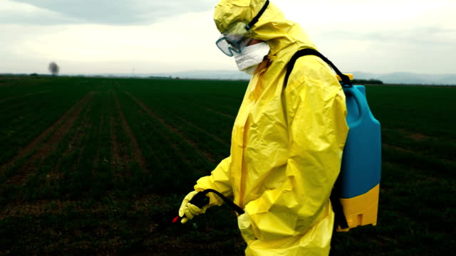 worker spraying toxic pesticides - insetticida video stock e b–roll