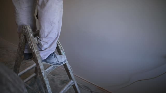 Worker standing on a ladder Worker standing on a ladder house painter stock videos & royalty-free footage