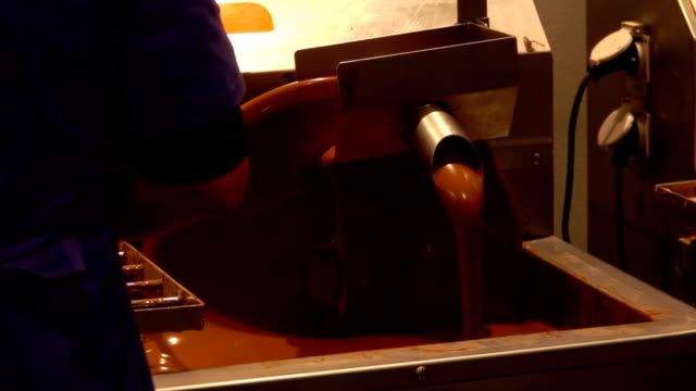 Worker stands near confectionery chocolate mixer - video