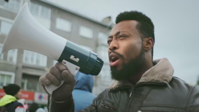 vídeos de stock e filmes b-roll de worker strike. african american rebel shouts in megaphone. loudspeaker scream. - megafone