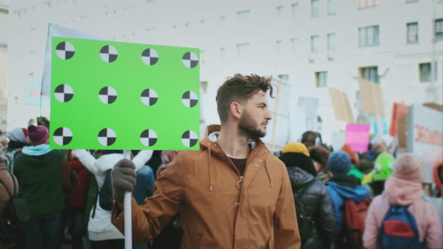 Worker strike. Man with blank banner. Background of crowd of people. Mock up 4k. video