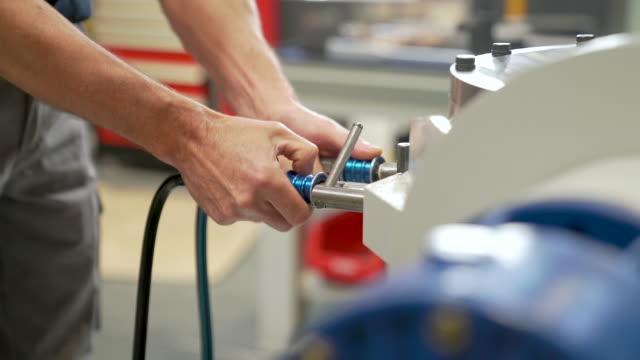 worker testing gears with high pressure machine. - lega metallica video stock e b–roll