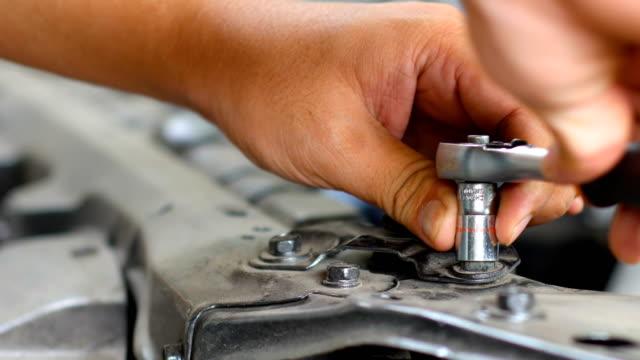 worker tightening bolt in car engine room, car repairing,  dolly shot - затягивание стоковые видео и кадры b-roll