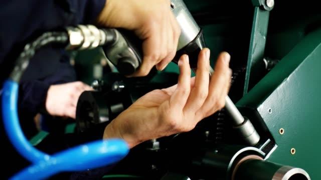 worker tightens bolt assembling compressor in workshop - klucz ręczne narzędzie filmów i materiałów b-roll