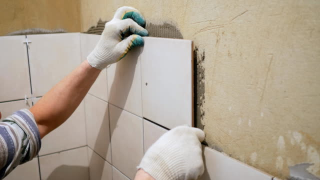 Worker tiler puts ceramic tiles on a wall video