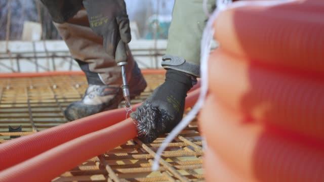 フックを結ぶワイヤーを使用して鋼のフレームにプラスチック製のパイプを結ぶ労働者 ビデオ