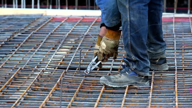vídeos y material grabado en eventos de stock de trabajador anudar el rebar en el sitio de construcción de cobre - pinzas utensilio para servir