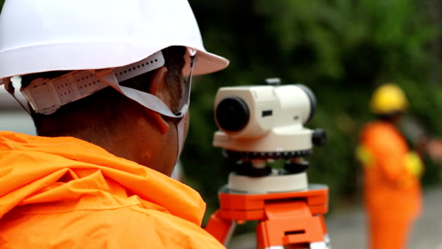 worker use surveyor's telescope at new road construction site worker use surveyor's telescope at new road construction site survey stock videos & royalty-free footage