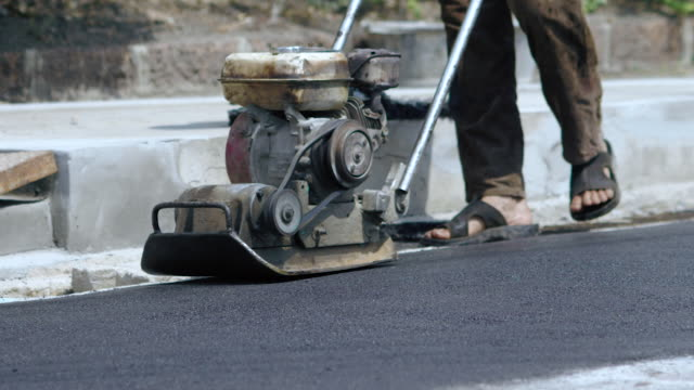Worker use the Ground Compactor for construction road