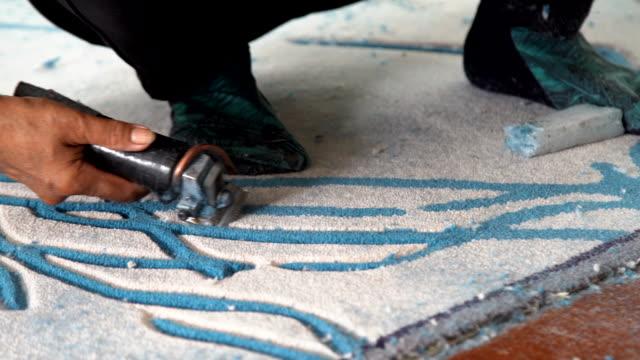 worker används cutting mattor verktyg för dekorera carpet handgjorda. - väva bildbanksvideor och videomaterial från bakom kulisserna