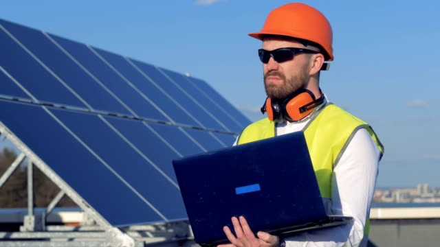 Worker uses his laptop, while examining the solar panels on the roof. 4K.