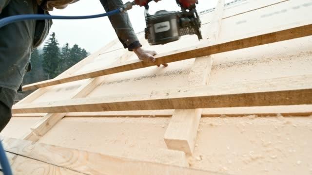 vídeos de stock e filmes b-roll de worker using a pneumatic nail gun to drive nails through batten on the roof - telhado