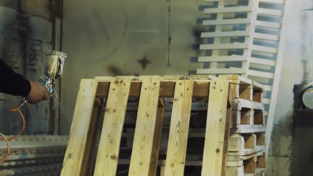 vídeos y material grabado en eventos de stock de trabajador por medio de aerógrafo para pintar plataforma de madera blanco en el taller - letra s