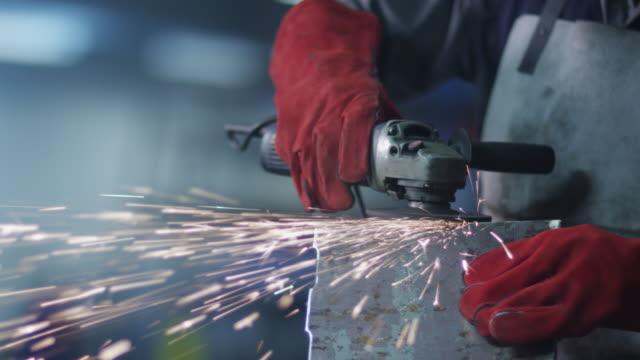 stockvideo's en b-roll-footage met werknemer met haakse slijper in fabriek - metaalbewerking