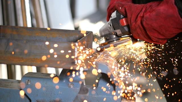 SLOW MOTION. Worker using industrial grinder.