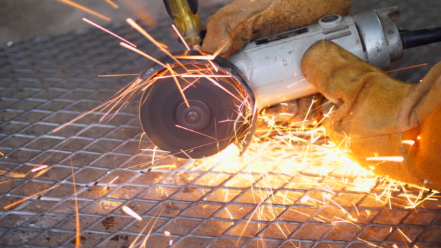 Worker Using Machine Cutting Net Metal with Sparking