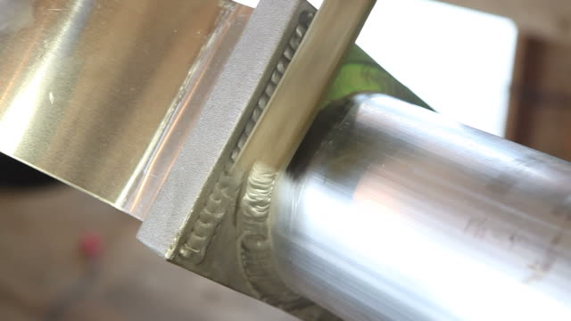 Worker Using Wire Brush to Clean Aluminum TIG Weld A worker is using a wire brush to clean a TIG (Tungsten Inert Gas) weld on aluminum pipe in preparation for another pass of the welder. pipefitter videos stock videos & royalty-free footage