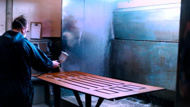 Worker varnishing wooden door video