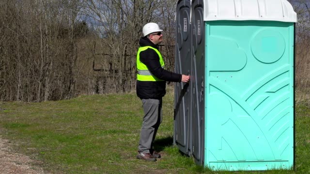stockvideo's en b-roll-footage met werknemer te wachten in de buurt van draagbaar toilet - cell phone toilet