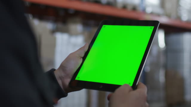 arbeiter walking in logistics warehouse holding tablet mit green screen in händen - querschnitt stock-videos und b-roll-filmmaterial