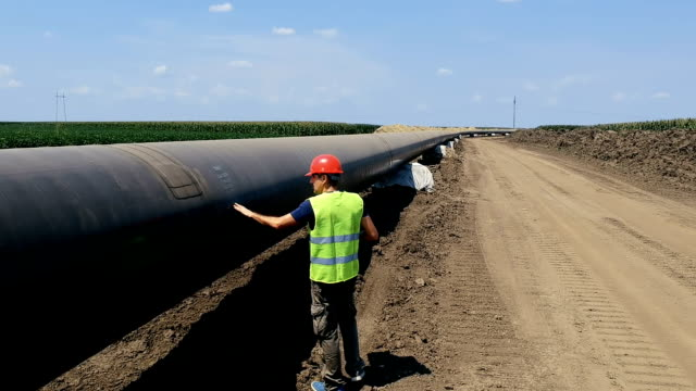 Worker Walking Next to Oil Pipeline - Aerial Drone Tracking Shot Engineer Checking Petrochemical Oil/Gas Pipeline at Construction Site. Pipeline under construction. oil industry stock videos & royalty-free footage