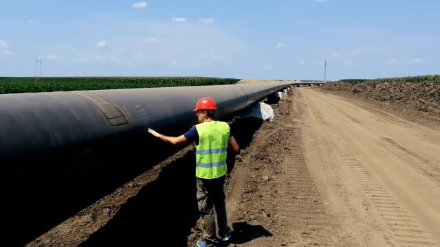 worker walking next to oil pipeline - aerial drone tracking shot - дистанционный стоковые видео и кадры b-roll