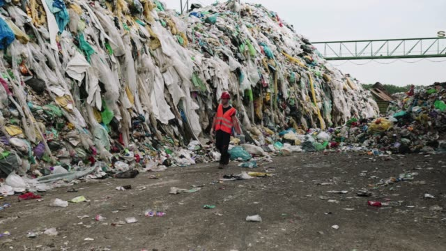 worker walking past huge piles of garbage at waste disposal dump - словения стоковые видео и кадры b-roll