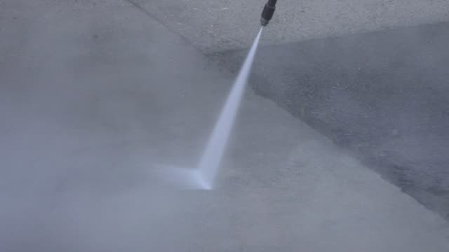 Worker washing the floor with a high pressure washing machine. video