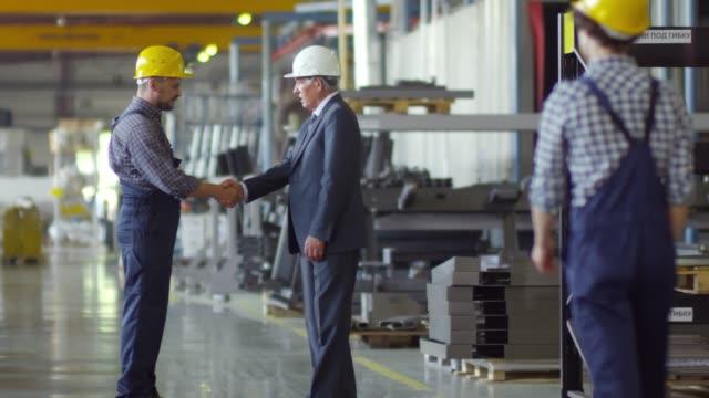 arbeiter begrüßt führungskraft in fabrik - bauarbeiterhelm stock-videos und b-roll-filmmaterial